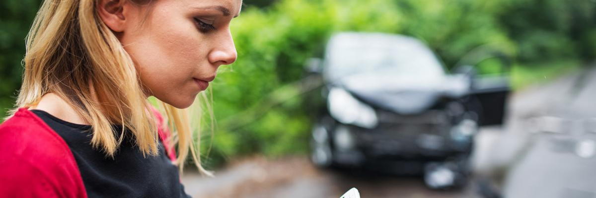 Young woman on the phone after after a car accident.