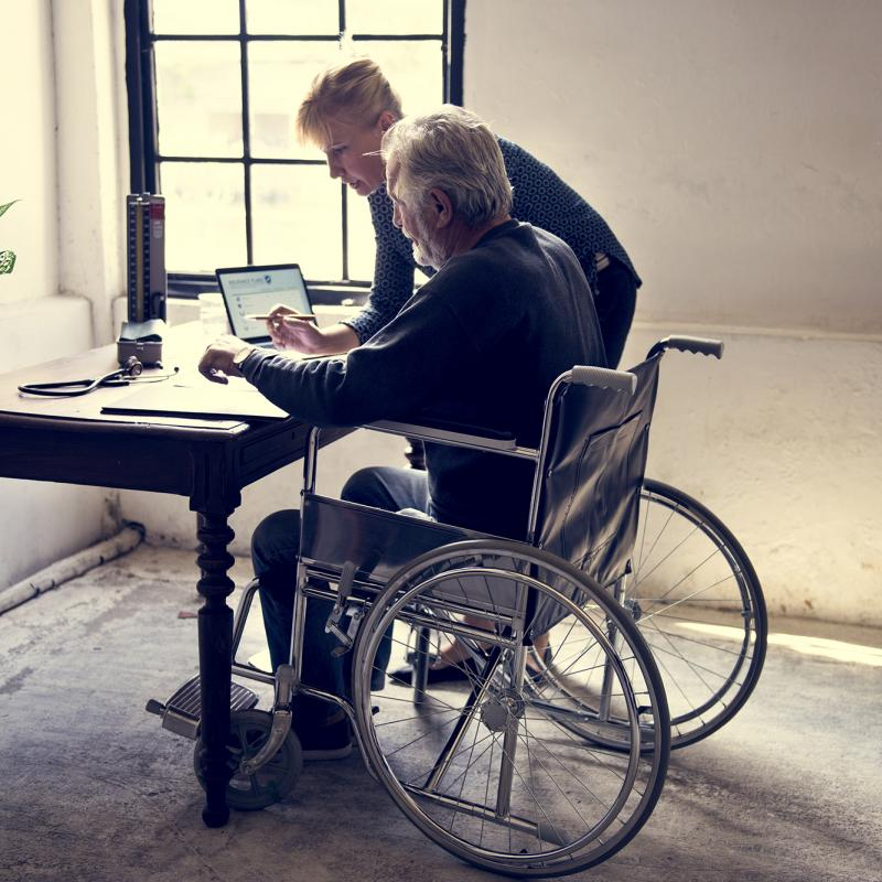 Man in wheelchair getting help picking life insurance